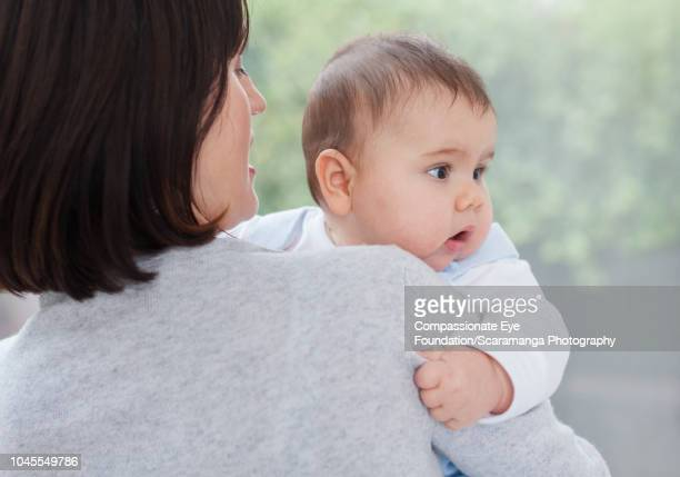 """mother holding baby boy by window - """"compassionate eye"""" stock pictures, royalty-free photos & images"""
