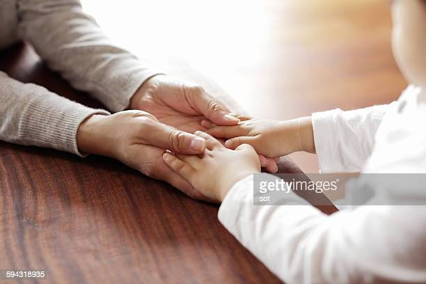 Mother holding baby boy hand,close up