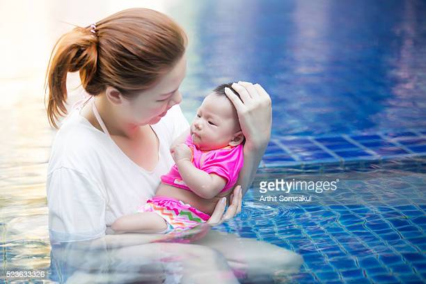 mother holding baby boy (0-6 months) in pool - 0 11 monate stock-fotos und bilder