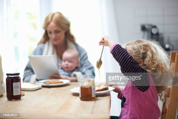 Mother holding baby boy, looking at digital tablet, sitting at kitchen table with young daughter, having breakfast