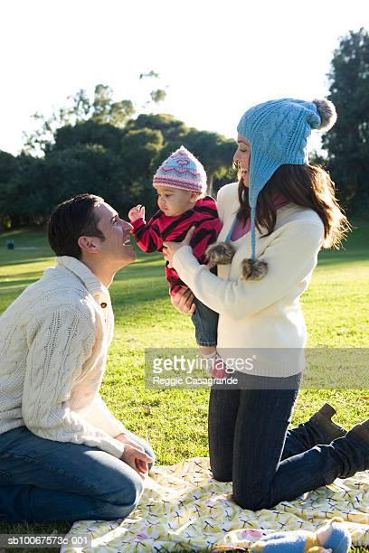 mother holding baby boy (6-11 months) up to father in park - 6 11 months stock pictures, royalty-free photos & images