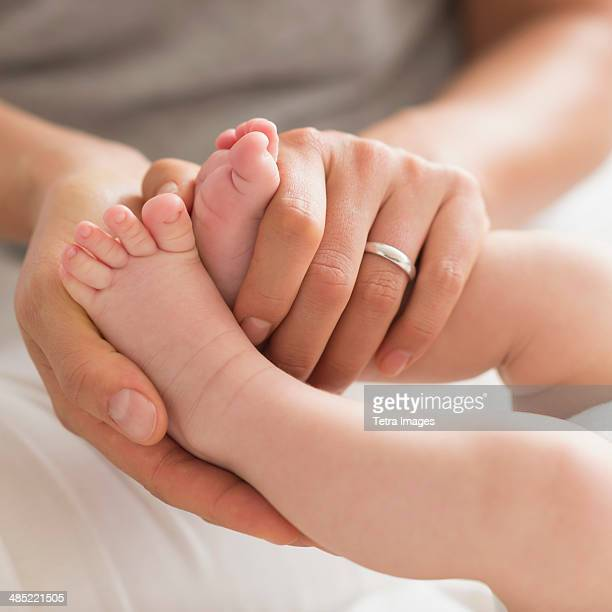 Mother holding baby boy's (2-5 months) feet