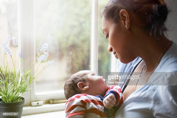 mother holding baby by window