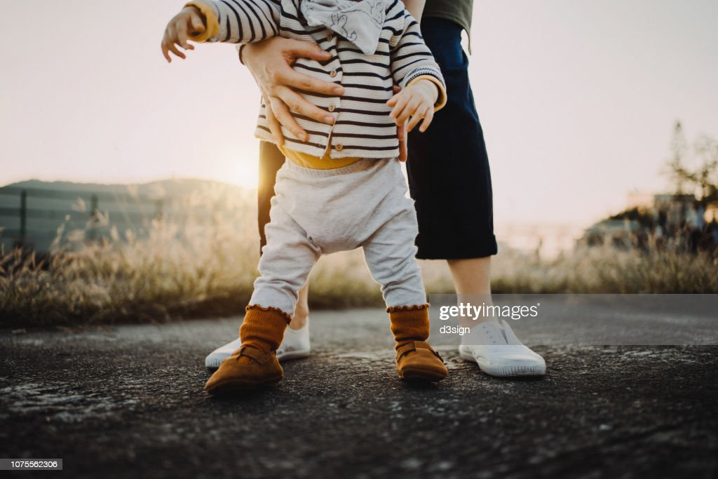 Mother holding baby daughter's body helping her to take her first step in life : Stock Photo