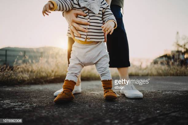 mother holding baby daughter's body helping her to take her first step in life - asian baby stockfoto's en -beelden
