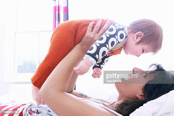 mother holding baby face to face on bed
