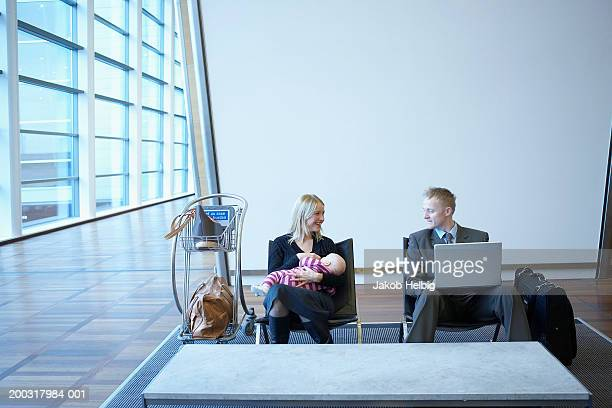 Mother holding baby girl (2-5 months) and businessman in airport lounge