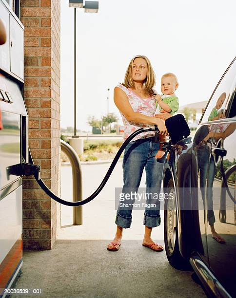 Mother holding baby girl (12-15 months) and pumping gas into car