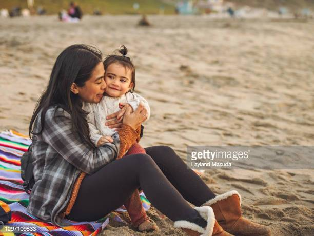 mother holding baby girl on beach sand - torrance stock pictures, royalty-free photos & images