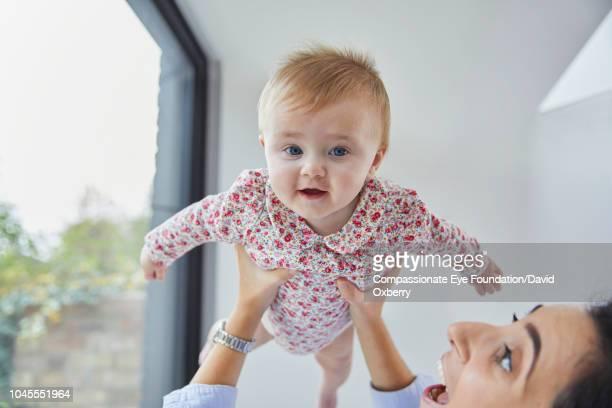 Mother holding baby girl overhead