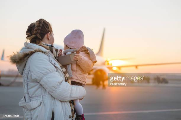 mother holding baby girl runway in front of plane - toddler at airport stock pictures, royalty-free photos & images