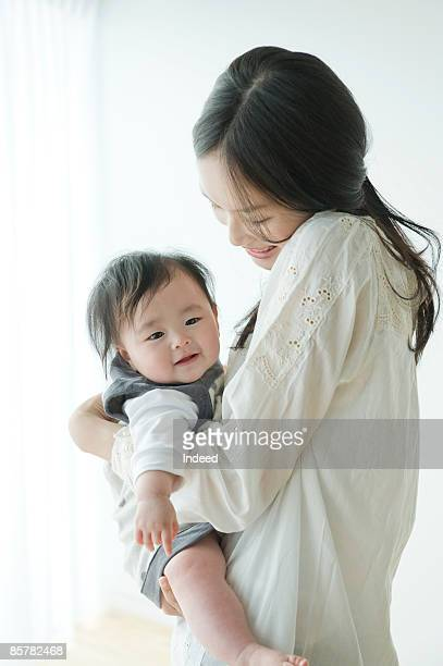 Mother holding baby girl, smiling, side view