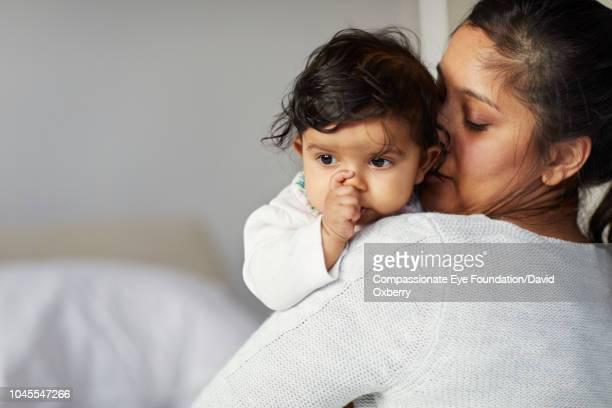 mother holding baby girl sucking thumb - chupando dedo - fotografias e filmes do acervo