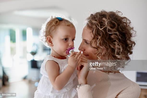 mother holding baby girl with pacifier at home - bico - fotografias e filmes do acervo