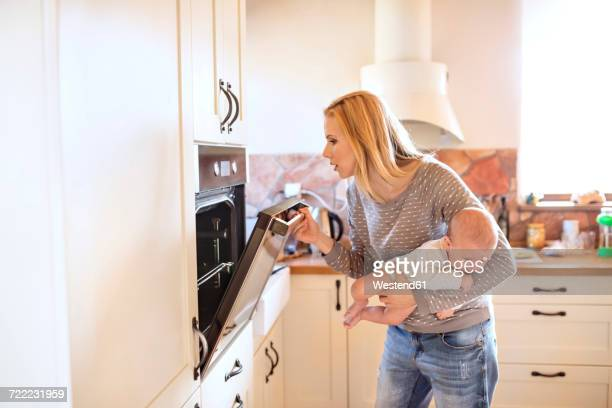 mother holding baby in kitchen looking in oven - stay at home mother stock pictures, royalty-free photos & images