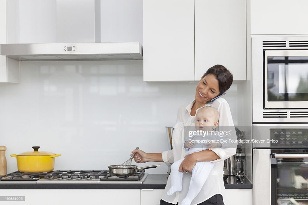 Mother holding baby in kitchen using mobile phone : Stock Photo