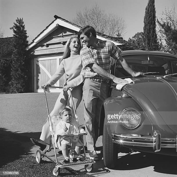 Mother holding baby in stroller, father cleaning car