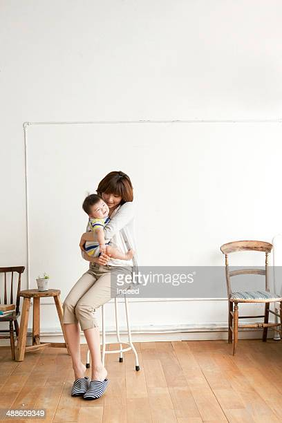 Mother holding baby on chair