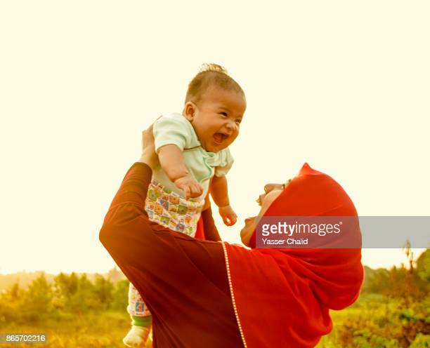 mother holding baby - muslim mother stock pictures, royalty-free photos & images