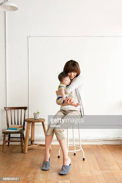 Mother holding baby, sitting on chair