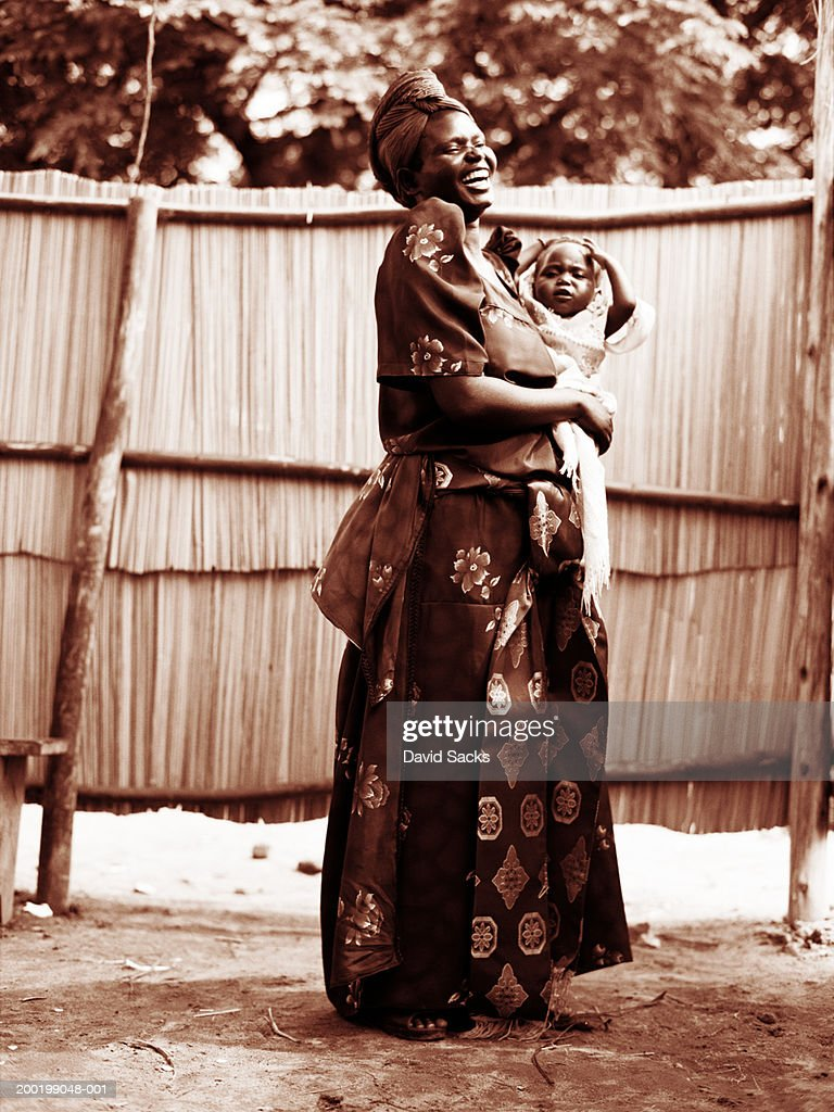 Mother holding baby (6-9 months), smiling (sepia tone) : Foto de stock