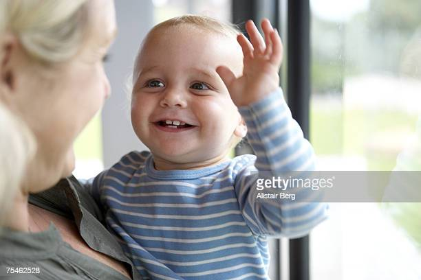 Mother holding baby son (18-21 months) by window