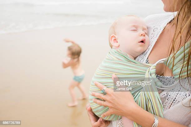 Mother holding baby son (6-11 months), daughter (2-3) dancing on beach