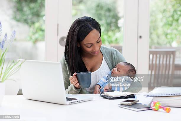 mother holding baby son, with laptop and coffee cup - pregnant coffee stock pictures, royalty-free photos & images