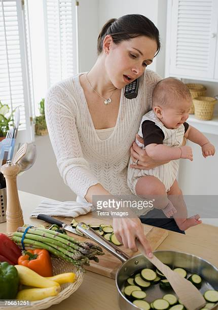 Mother holding baby, talking on telephone and cooking
