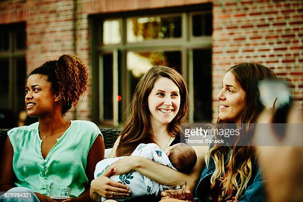 Mother holding baby while hanging out with friends