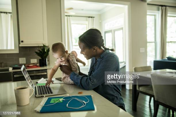 mother holding baby while using laptop/working from home - mulheres de idade mediana - fotografias e filmes do acervo