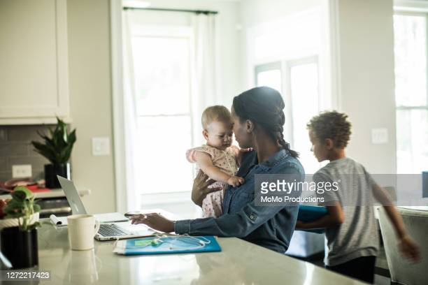 mother holding baby while using laptop/working from home - mother stock pictures, royalty-free photos & images