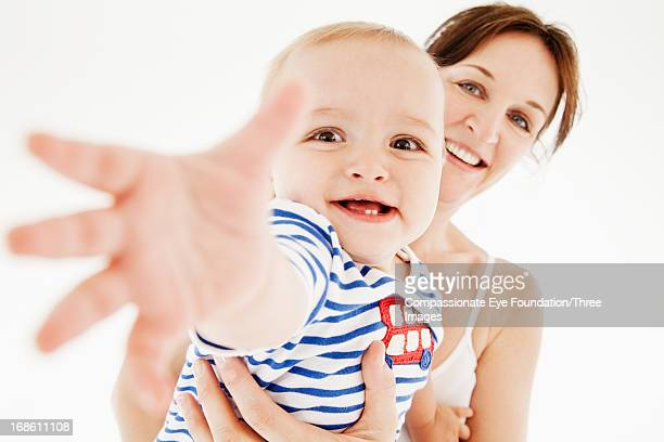 Mother holding baby with outstretched hand