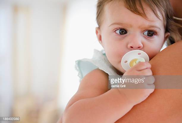 Mother holding baby with pacifier
