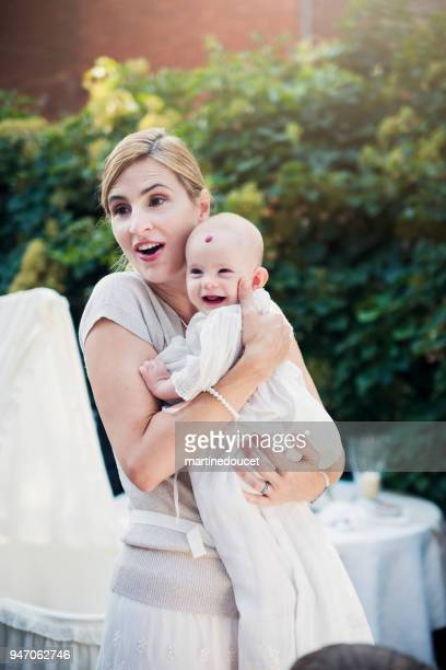 mother holding baby with traditionnal baptism robe. - hemangioma imagens e fotografias de stock