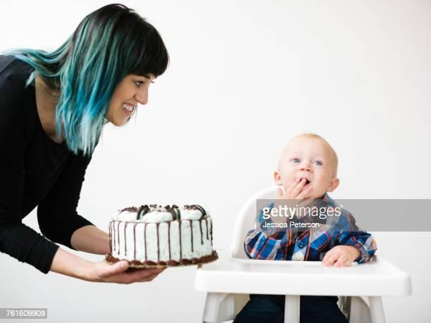 mother holding birthday cake for son (12-17 months) - first birthday imagens e fotografias de stock