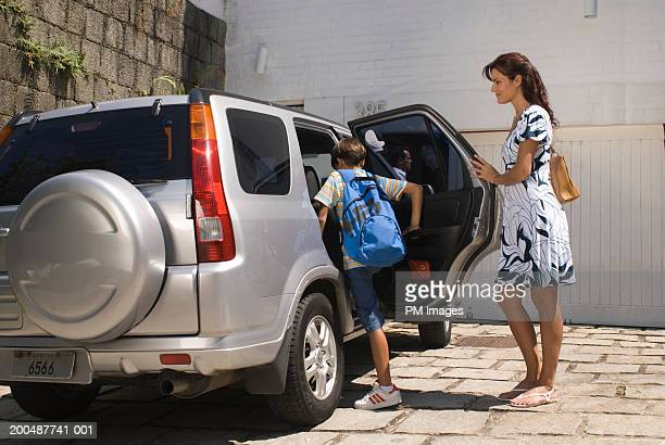 Mother holding car door open, boy (10-12) getting into car