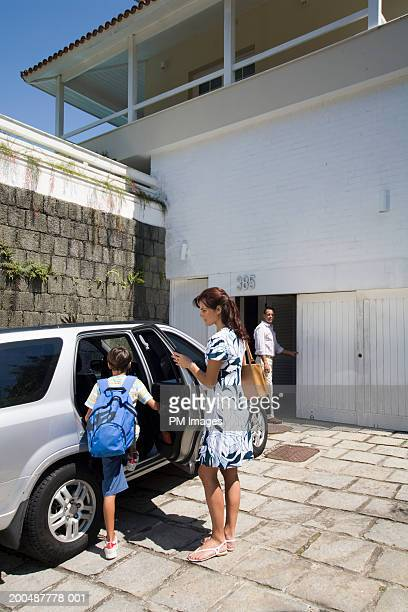 Mother holding car door open for son (10-12), father in background