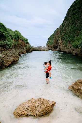 Mother holding child in tropical water, Okinawa, Japan - gettyimageskorea