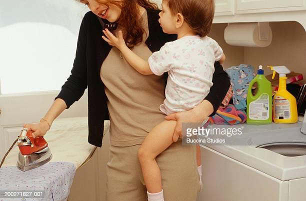 Mother holding child (21-24 months) whilst ironing in laundry room, mid section