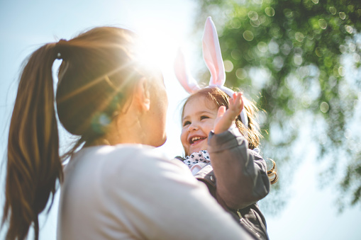Mother holding child with bunny ears 664043792