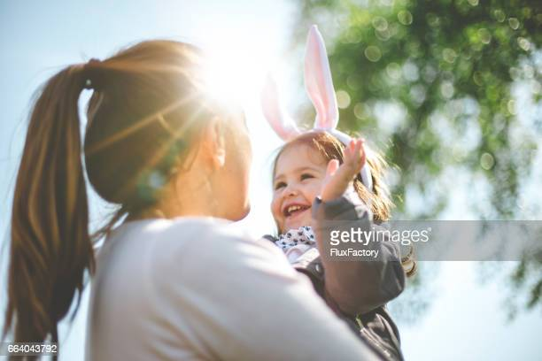 mother holding child with bunny ears - pasqua foto e immagini stock