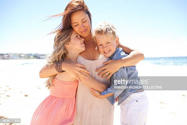 Mother holding children under arms on beach