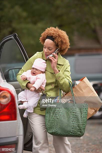 Mother holding crying baby while talking on cell phone
