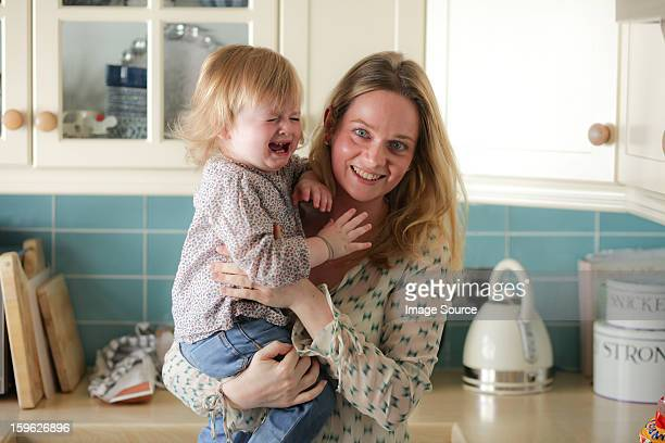 Mother holding crying daughter