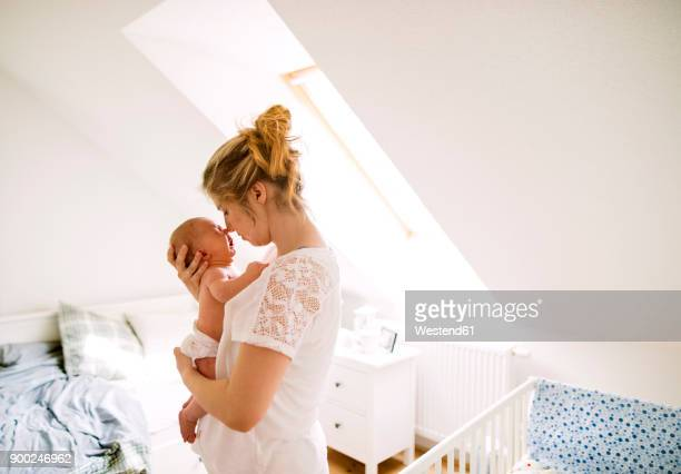 Mother holding crying little baby at home