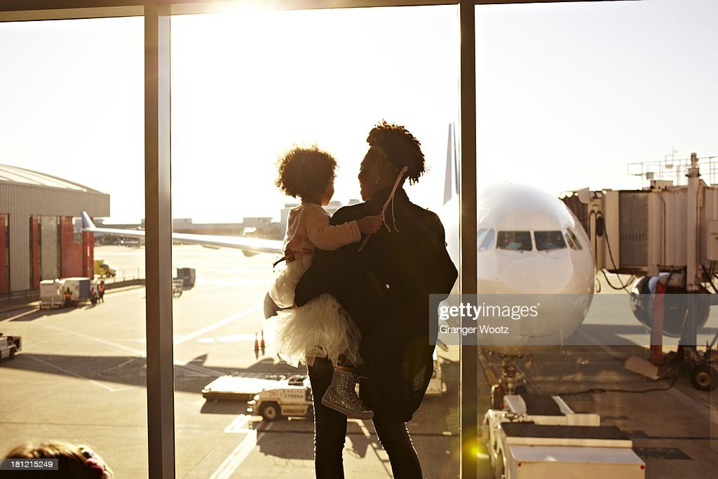 Mother holding daughter at airport : Stock Photo