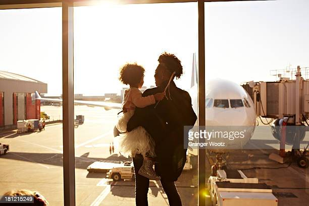 mother holding daughter at airport - family with one child stock pictures, royalty-free photos & images