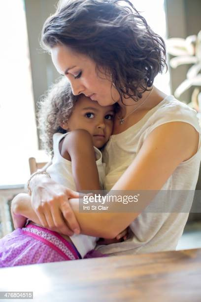 Mother holding daughter at table