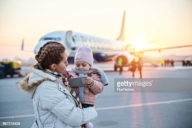 Mother holding daughter at the airport